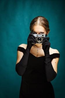 Das mädchen in einem schwarzen abendkleid mit einer kamera in der hand