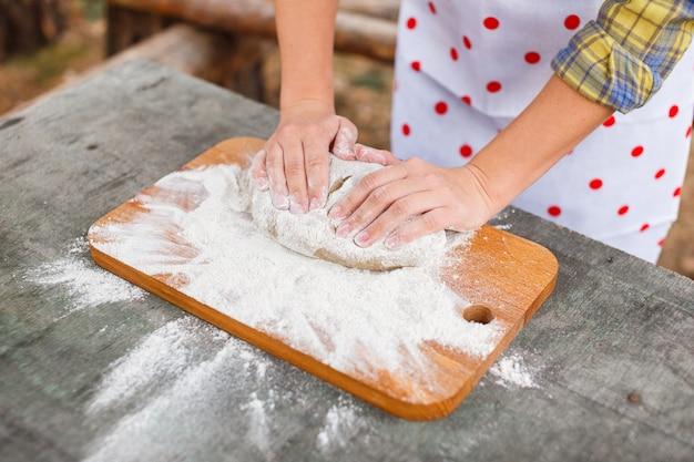 Das mädchen in einem weißen schutzblech bereitet den teig auf einem schneidebrett vor