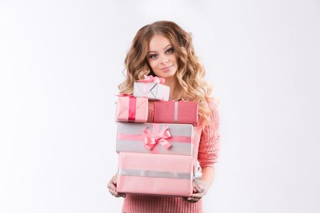 Das mädchen in einer rosa bluse, die rosa kästen mit geschenken auf einem weißen hintergrund hält