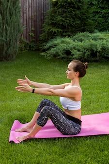 Das mädchen ist in der nähe des hauses mit yoga beschäftigt. sie streckt den rücken und überwacht ihre haltung