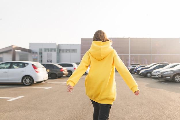 Das mädchen ist in einem gelben hoodie zurück und geht die straße entlang