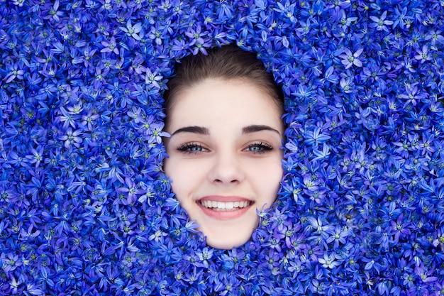 Das mädchen ist mit blauen frühlingsblumen bedeckt, das mädchen schaut unter den blumen hervor.