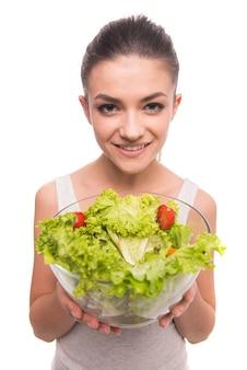 Das mädchen lächelt und hält den salat in seinen händen.