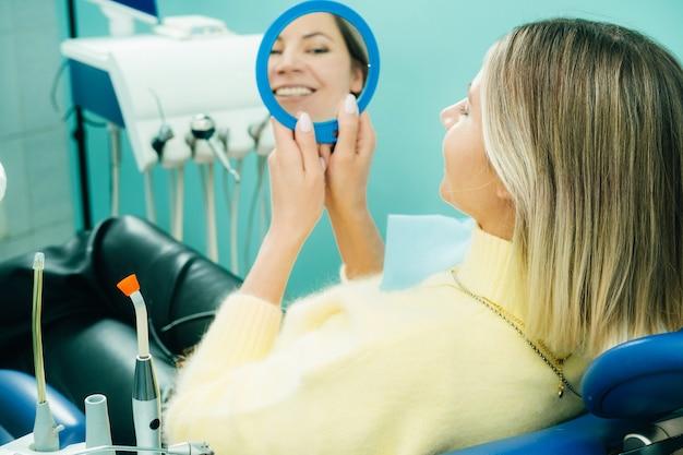Das mädchen lächelt und schaut in der zahnmedizin in den spiegel.