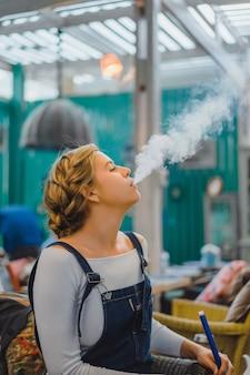 Das mädchen läßt rauch aus einer wasserpfeife heraus