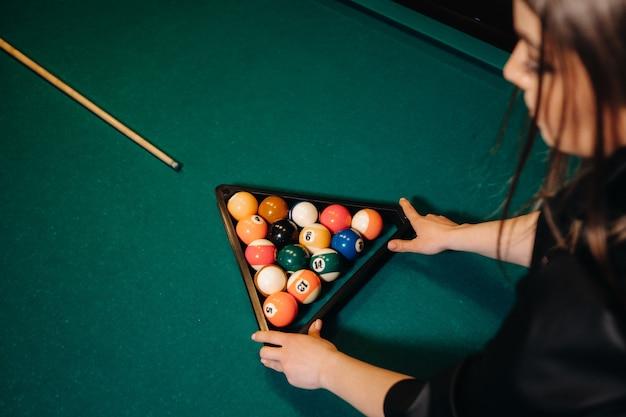 Das mädchen legt billardkugeln aus, um das spiel im billardclub zu beginnen