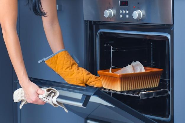 Das mädchen legt ein backblech in den ofen. Premium Fotos