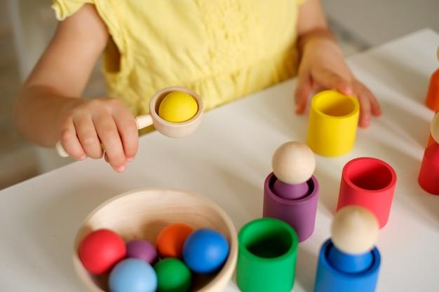 Das mädchen legt farbige kugeln in einen löffel und wirft sie in tassen der entsprechenden farbe