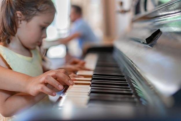 Das mädchen lernt klavier spielen, hört aufmerksam den anweisungen des lehrers zu, drückt die tasten und versucht, die melodie zu wiederholen und auswendig zu lernen.