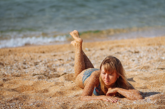 Das mädchen liegt am strand. großer blauer seehintergrund