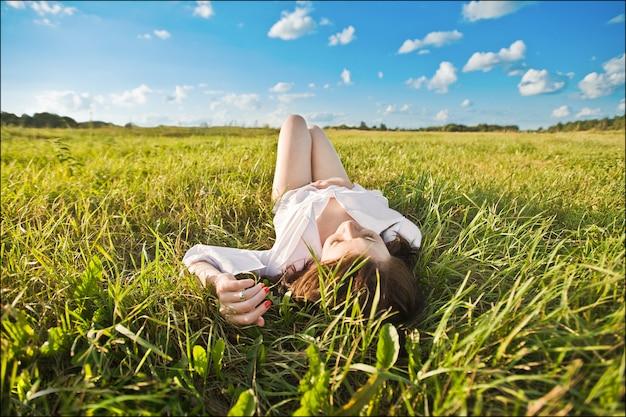 Das mädchen liegt im gras. glückliches lächelndes schönes mädchen, das unter gras und blumen liegt. auf einem blauen hintergrund.