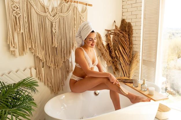Das mädchen macht sich eine massage mit einer bürste in der badewanne. sie hat schöne gebräunte beine. sie macht lymphatische anti-cellulite-massage