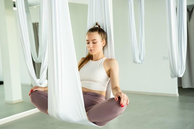 Das mädchen meditiert in einer weißen hängematte. sie praktiziert fliegenyoga. konzept für körperliche und geistige gesundheit