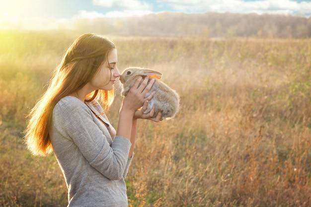 Das mädchen mit dem kaninchen glückliches kleines mädchen, das nettes flaumiges häschen hält freundschaft mit osterhasen