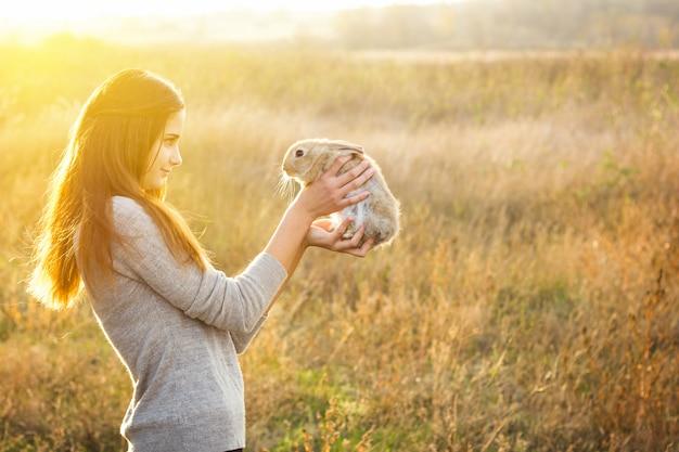 Das mädchen mit dem kaninchen glückliches kleines mädchen, das nettes flaumiges häschen hält