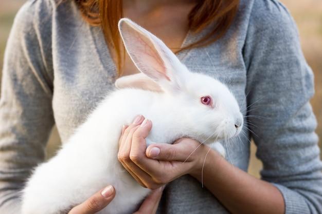 Das mädchen mit dem kaninchen.glückliches kleines mädchen, das niedlichen flaumigen häschen hält. freundschaft mit osterhasen