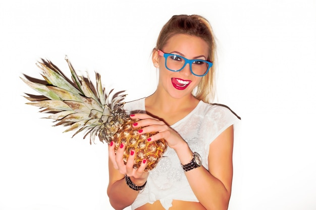 Das mädchen mit den roten lippen eine ananas anhält