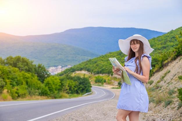 Das mädchen mit der karte sucht die straße. artikel über trampen. sommerferien.
