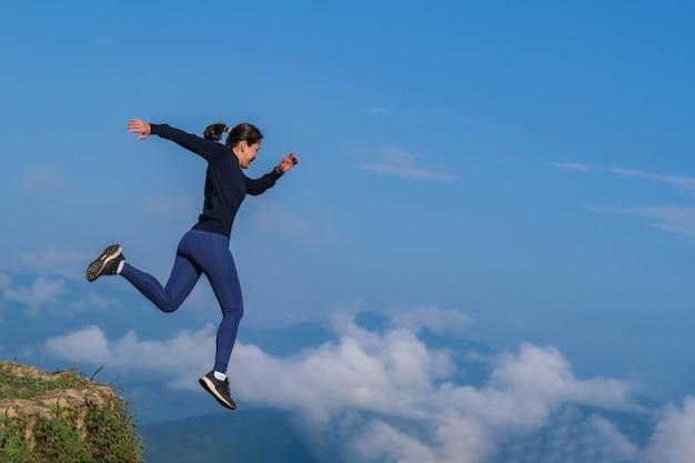 Das mädchen rannte, sprang von einem hohen platz und rannte auf einem bergigen feld.