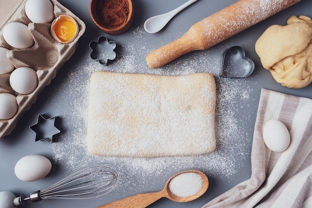 Das mädchen rollt den teig mit einem hölzernen nudelholz aus, um cupcakes oder kekse zu machen.