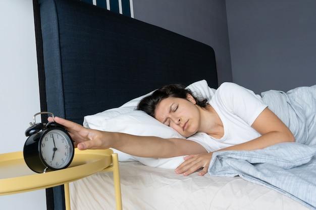 Das mädchen schaltet den nervigen wecker aus, um weiter zu schlafen. schlaf noch ein bisschen. es ist ein harter morgen. zeit aufzuwachen.