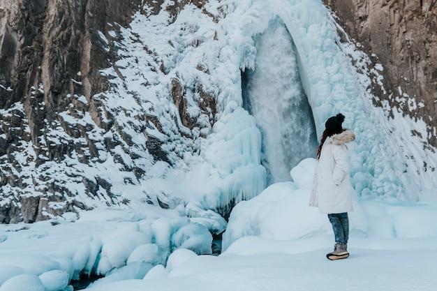 Das mädchen schaut auf den wasserfall. reisender auf dem hintergrund eines wasserfalls im winter.