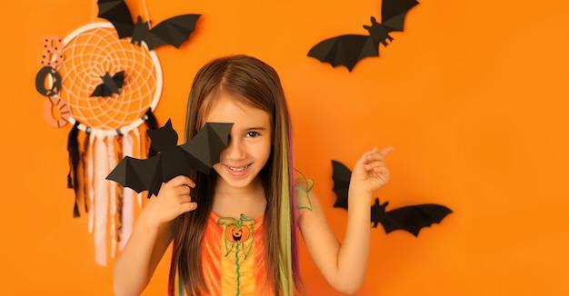Das mädchen schließt das auge mit einer fledermaus, die mit der anderen hand auf das konzept von halloween zeigt