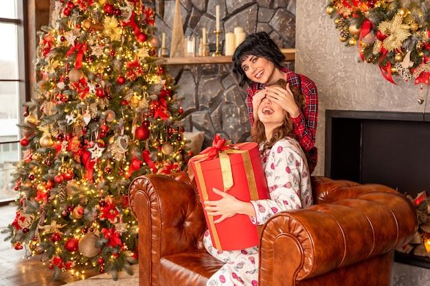 Das mädchen schließt die augen ihrer freundin, um sie mit einem geschenk zu überraschen. freundin, die in ihren händen großes rotes geschenk mit goldenen bändern hält.