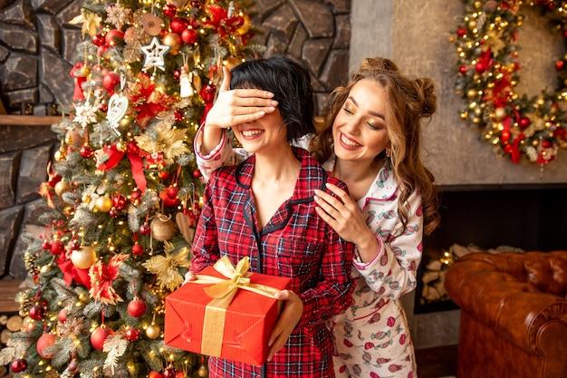 Das mädchen schließt die augen ihrer freundin, um sie mit einem geschenk zu überraschen. freundin, die in ihren händen rotes geschenk mit goldenen bändern hält.