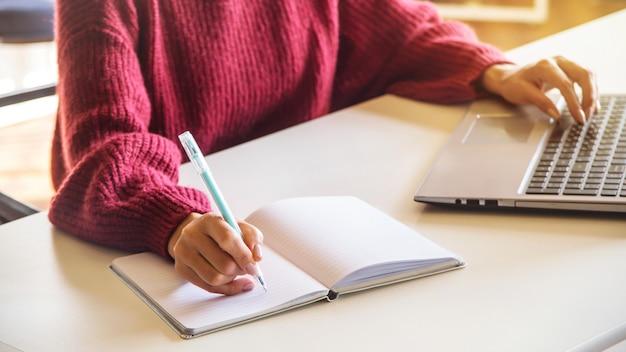 Das mädchen schreibt in ein notizbuch und arbeitet an ihrem laptop an einem weißen tisch in hellem coworking.
