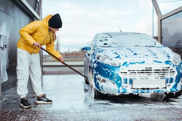 Das mädchen selbst in der autowaschanlage wäscht das auto mit einer bürste