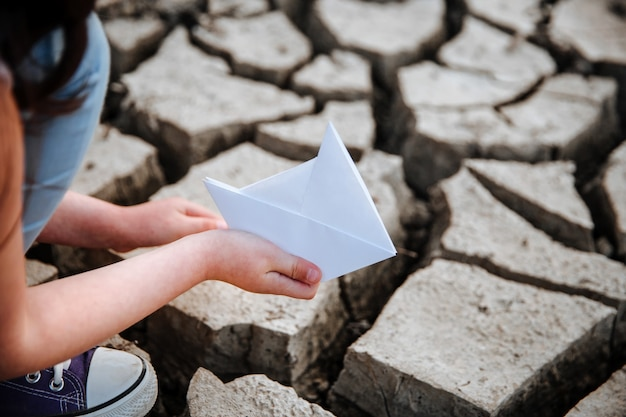 Das mädchen senkt das papierboot auf den trockenen, rissigen boden wasserkrise und klimawandelkonzept