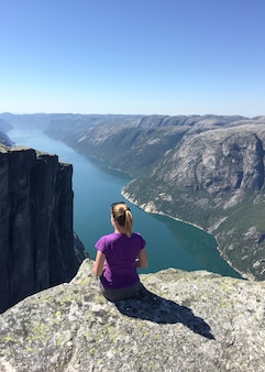 Das mädchen sitzt am rand einer klippe und schaut auf den fjord