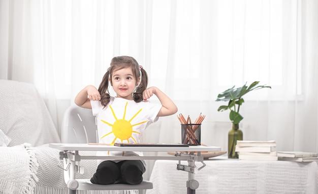 Das mädchen sitzt am tisch und macht hausaufgaben. das kind lernt zu hause. heimschulkonzept.