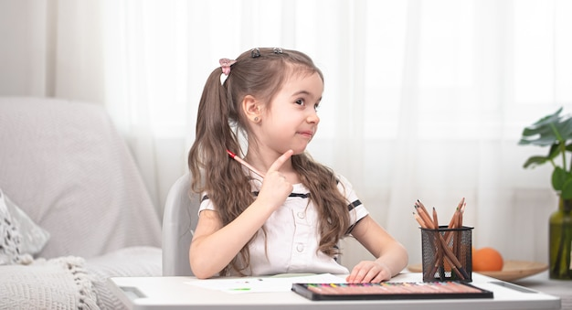 Das mädchen sitzt am tisch und macht hausaufgaben. das kind lernt zu hause. heimunterricht. platz für text.