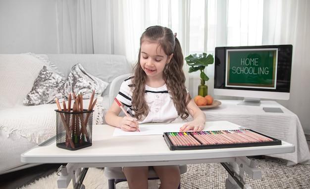 Das mädchen sitzt am tisch und macht hausaufgaben. das kind lernt zu hause. heimunterricht und bildung