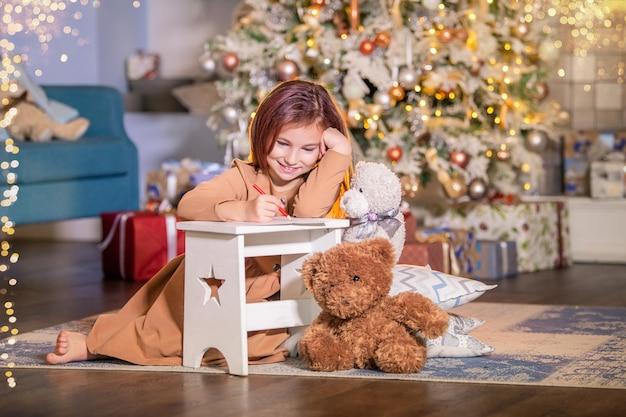 Das mädchen sitzt auf den knien neben dem weihnachtsbaum und schreibt einen brief an den weihnachtsmann.