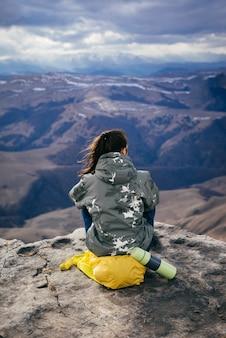 Das mädchen sitzt auf einem gelben rucksack am rand der klippe und genießt die bergnatur, in der thermoskanne heißen tee