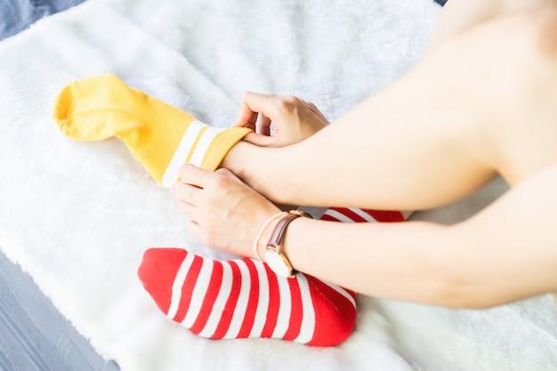 Das mädchen sitzt auf einem weißen teppich und zieht socken an, gelbe punktieren rote seite.