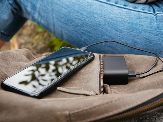 Das mädchen sitzt in der natur und wartet darauf, dass das smartphone von der power bank aufgeladen wird
