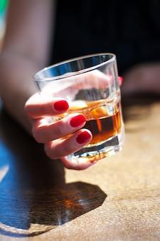 Das mädchen sitzt in einem café und hält ein glas whisky in der hand