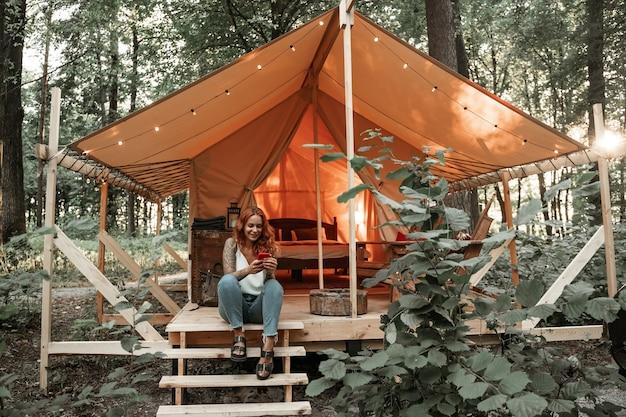 Das mädchen sitzt neben dem zelt und chattet messaging-streaming auf dem smartphone, postet, liket in sozialen medien. reisen sie außerhalb der stadt im wald. camping. low-budget-urlaub im glamping-zelt