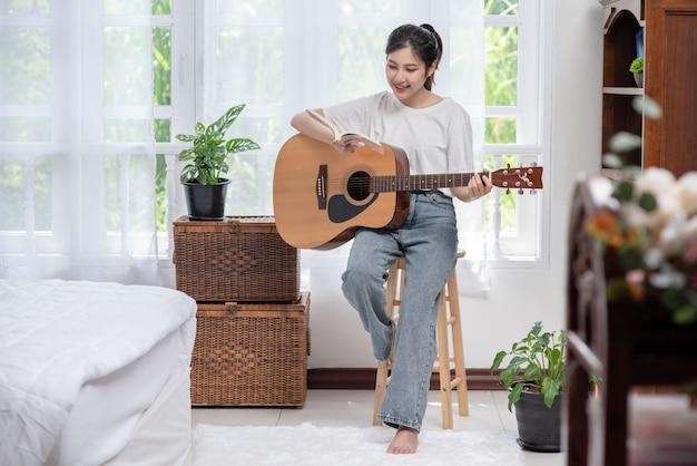 Das mädchen sitzt und spielt gitarre auf dem stuhl.
