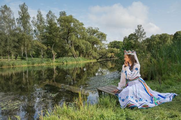Das mädchen sitzt vor dem hintergrund der belarussischen natur