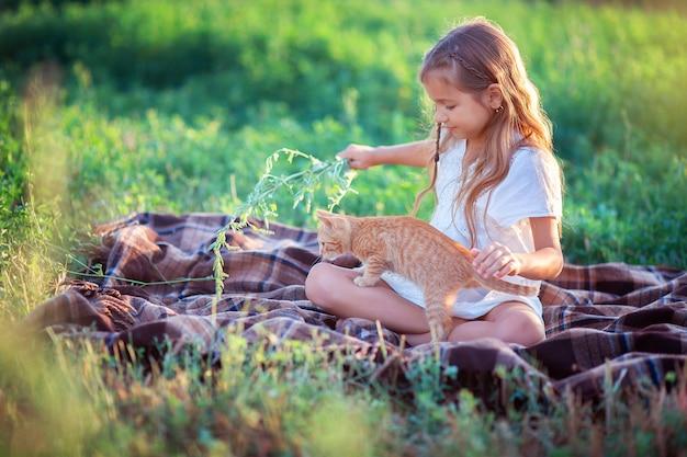 Das mädchen spielt mit einem ingwerkätzchen auf der straße im gras. landmädchen spielt mit einer katze. kind, das auf der farm ruht