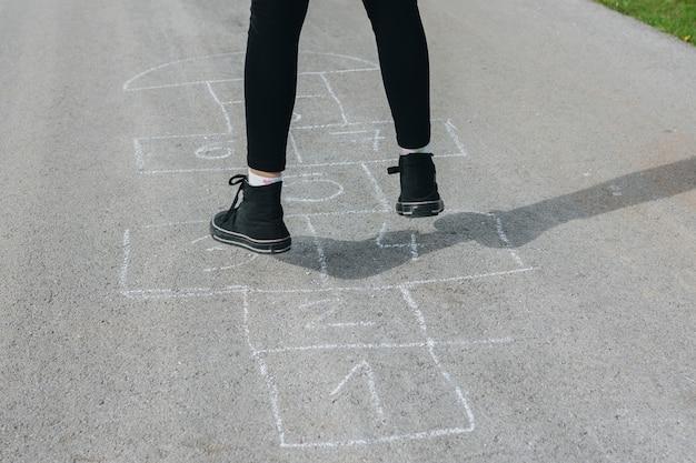 Das mädchen springend in die kreidekästen, die auf asphalt gezeichnet werden