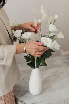 Das mädchen stellt blumen in eine vase. dekoartive weiße blumen in einer vase. künstliche blumen.