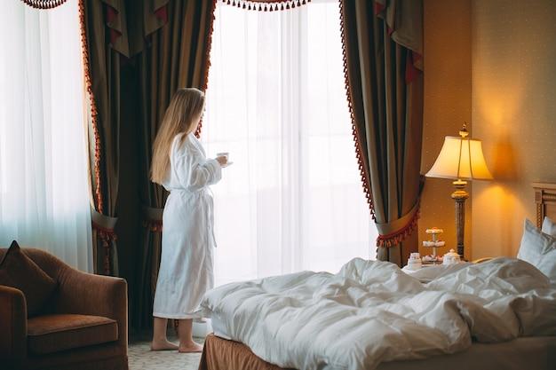 Das mädchen stit am fenster und trinkt morgenkaffee im hotelzimmer oder zu hause.