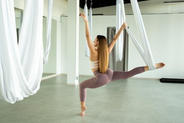 Das mädchen streckt ihr bein mit einer hängematte aus sie praktiziert fliegenyoga
