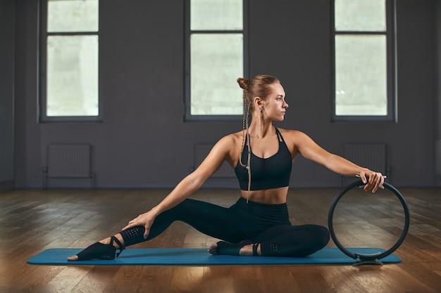 Das mädchen trainiert ihre hände mit einem fitness-expander im fitnessstudio, macht liegestütze, trainiert den oberkörper, die schultern, die brust und den trizeps.